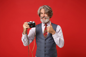 Smiling elderly gray-haired mustache bearded man in classic shirt vest tie isolated on red background. People lifestyle concept. Mock up copy space. Hold retro vintage photo camera, showing thumb up.