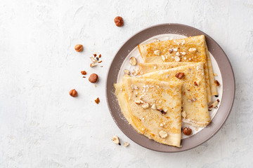 Crepes with hazelnuts and powdered sugar on plate on white concrete background. Top view. Copy space.