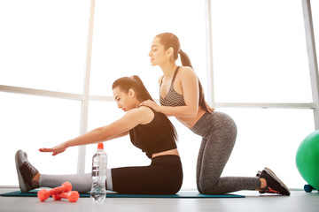 Picture of two well-built young women stretching. One model help another to warm up. She stand behind her and oush on back. Asian woman try to do her best.