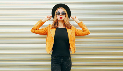 Stylish woman model posing wearing yellow jacket, black round hat on metal wall background