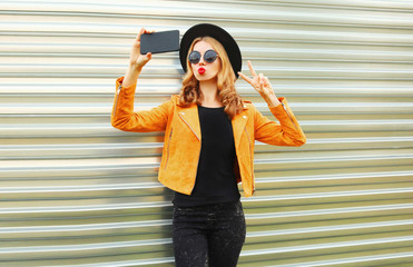 Stylish woman taking selfie picture by smartphone wearing yellow jacket, black round hat on metal wall background