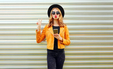Stylish young woman with phone wearing yellow jacket, black round hat posing on metal wall background