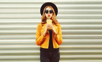Stylish woman drinking juice wearing yellow jacket, black round hat on metal wall background