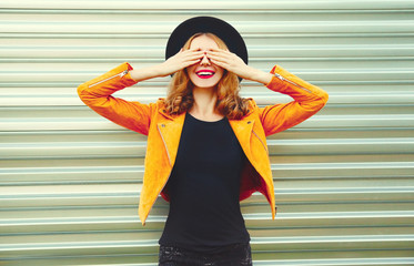 Portrait happy smiling woman covering her eyes with her hands making wish wearing yellow jacket, black hat on metal wall background