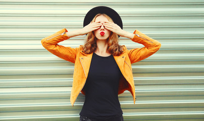 Portrait happy woman covering her eyes with her hands making wish wearing yellow jacket, black hat on metal wall background