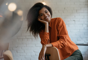 Authentic portrait of young cheerful African American woman with beautiful smiling face, curly hairstyle sitting on chair in modern cafe. Cute fashion model posing for pictures, laughing