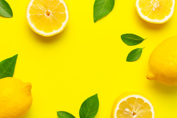 Creative background with fresh lemons and green leaves on bright yellow background. Top view flat...