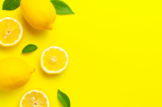 Creative background with fresh lemons and green leaves on bright yellow background. Top view flat lay copy space. Lemon fruit citrus minimal concept vitamin C. Composition with whole, slices of lemons
