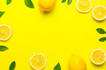 Wall Mural - Creative background with fresh lemons and green leaves on bright yellow background. Top view flat lay copy space. Lemon fruit citrus minimal concept vitamin C. Composition with whole, slices of lemons