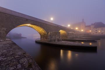 The Stone Bridge in the bavarian city of Regensburg before dawn covered in dense autumn fog