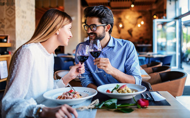 In de dag Restaurant Paste and red wine. Young couple enjoying lunch in the restaurant. Lifestyle, love, relationships, food concept
