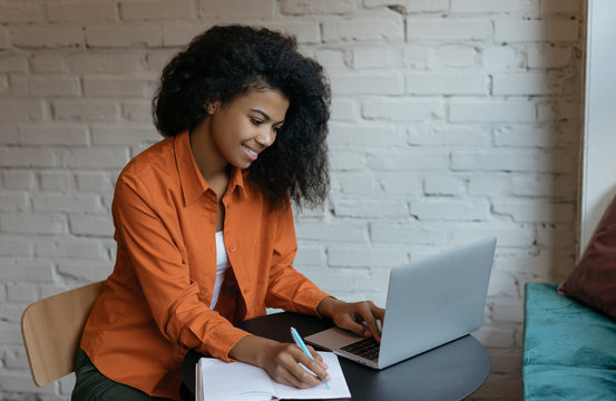 Successful university student studying, learning language, using laptop computer and internet. Young happy African American woman watching online business training courses on website, taking notes