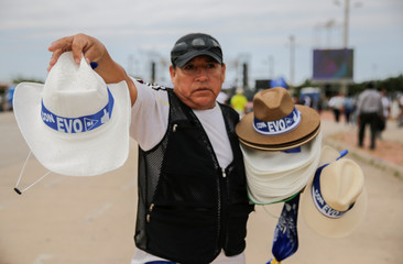 A man sells hats with electoral propaganda of Bolivia's President and current presidential candidate for the Movement for Socialism (MAS) party Evo Morales, during Morales' closing campaign rally, in Santa Cruz
