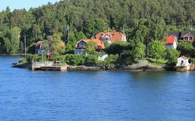 Printed kitchen splashbacks Khaki Modern swedish sea village. Modern model houses on a background of green forest.