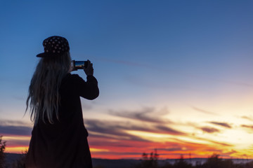 Back view of blonde girl, making photo of sunset with smartphone.