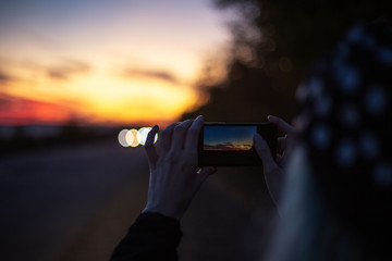 Close-up of female hands, making photo of sunset with smartphone.