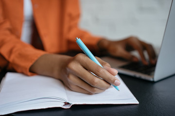 Closeup shot of university student hand using pen and writing in notebook, exam preparation, presentation, working project at workplace. Education concept. Woman taking notes, typing on keyboard