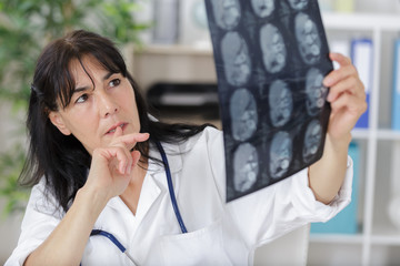 female doctor in doctors room looking at x-ray image