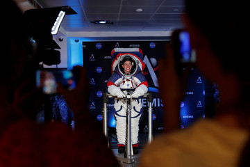 Visitors take pictures of Advanced Space Suit Engineer at NASA Kristine Davis as she wears the xEMU prototype space suit for the next astronaut to the moon by 2024,  during its presentation at NASA headquarters in Washington
