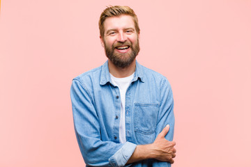 young blonde adult man laughing shyly and cheerfully, with a friendly and positive but insecure attitude Wall mural