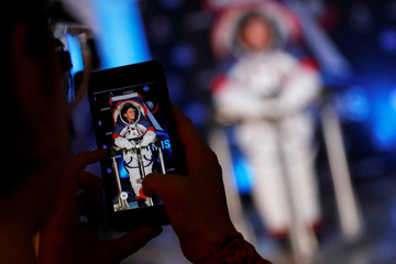 A visitors takes a picture of Advanced Space Suit Engineer at NASA Kristine Davis as she wears the xEMU prototype space suit for the next astronaut to the moon by 2024,  during its presentation at NASA headquarters in Washington