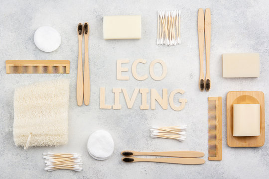 Eco living concept. Bamboo toothbrushes, handmade packaging free soap and shampoo bars, cotton buds pads, luffa on the white concrete marble table top, top view, selective focus