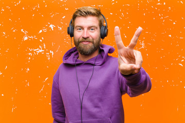 young blonde man dancing and listening music with headphones wearing a purple hoodie against damaged orange wall