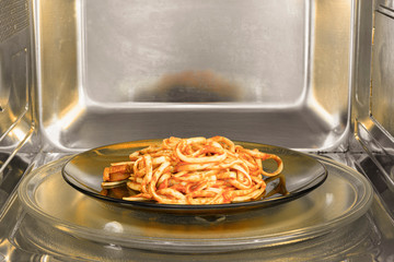 Pasta dish inside the microwave. Warming the pasta on the microwave. Reheating the food of dinner.