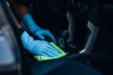 cropped view of car dealer wiping gear shifter with rag