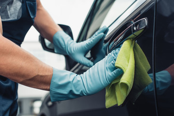 partial view of car cleaner wiping car door with rag