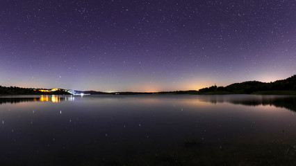 Night sky in the Dark Sky Alqueva Reserve. Astrophotography panorama above lagoon.