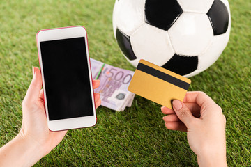 cropped view of female hands with smartphone and credit card near soccer ball and euro banknotes on green grass, sports betting concept
