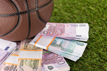 close up view of basketball ball near dollar and euro banknotes on green grass, sports betting concept