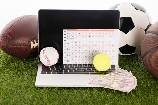 laptop near sports balls and betting list on green grass isolated on white, sports betting concept
