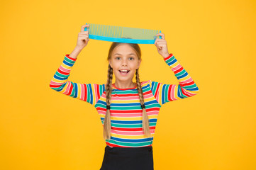 Professional equipment. Comb for tangled hair. Hairdresser supplies. Large comb. Girl long hair hold enormous comb. Hairdresser salon. Combing hair. Cheerful happy smiling little kid with giant comb