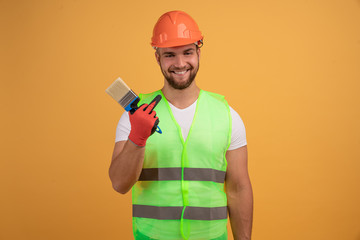 Smiling handyman wears orange hardhat and reflector waistcot, holds paint brush, paints wall and does repairing in flat, isolated over yellow background, shows a fuck to the camera.Painter man at work