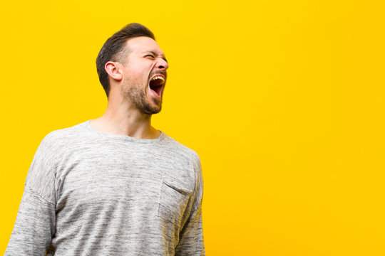young handsome man screaming furiously, shouting aggressively, looking stressed and angry against orange wall