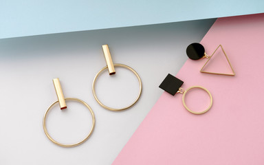 Two pairs of geometric shape golden earrings on pastel colors background
