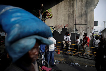 People look at a man painting a mural during a gathering of protesters to demand the resignation of Haitian President Jovenel Moise, in the streets of Port-au-Prince