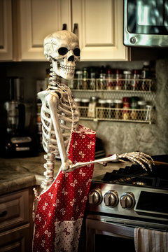 Halloween skeleton in the kitchen getting ready to prepare food for the holiday