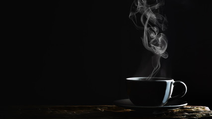beverage background of hot coffee, tea or chocolate in black cup on wooden plank in dark background