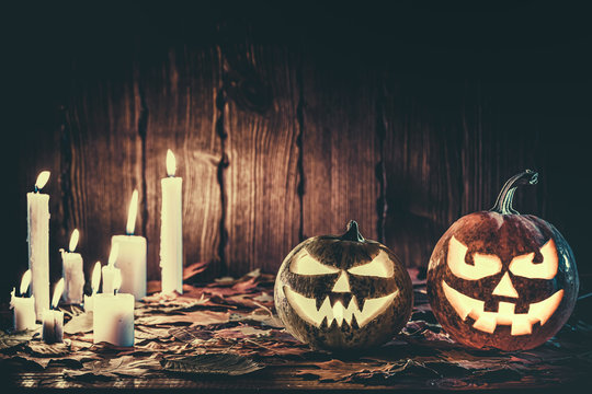 Halloween pumpkin with glowing face on a wooden background with candles