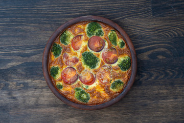 Ceramic bowl with vegetable frittata, simple vegetarian food. Frittata with egg, tomato, pepper, onion, broccoli and cheese on wooden table. Italian egg omelette