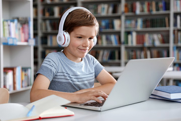 Little boy with headphones reading book using laptop in library