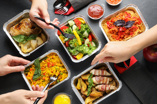 People eating from lunchboxes at grey table, top view. Healthy food delivery