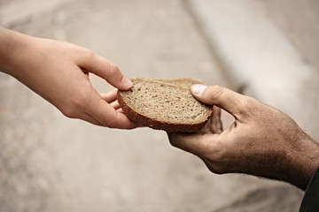 Woman giving poor homeless person pieces of bread outdoors, closeup