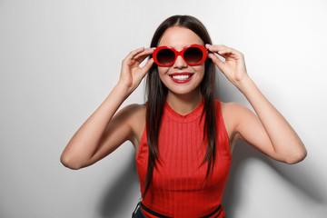 Beautiful woman in stylish sunglasses on light background