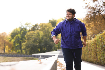 Young overweight man running in park. Fitness lifestyle