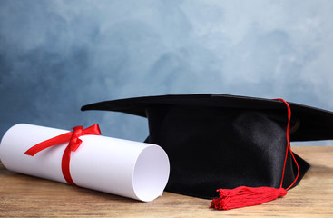 Graduation hat and student's diploma on wooden table against light blue background
