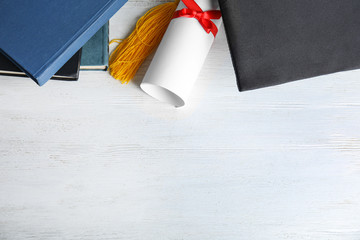 Flat lay composition with graduation hat and student's diploma on white wooden table, space for text